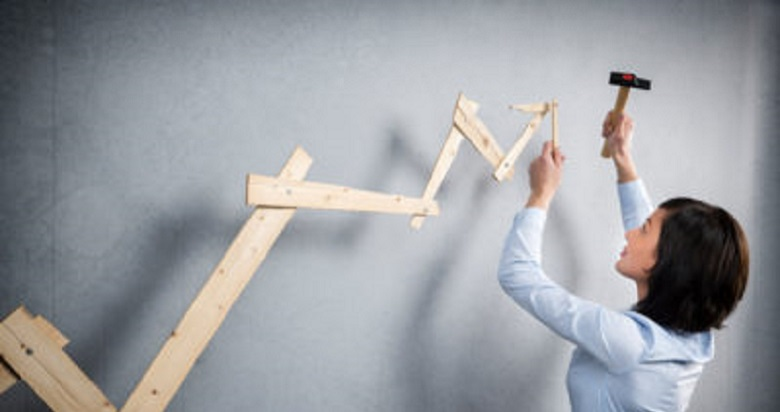 Concept: Building your own career or business. Young businesswoman installing upward arrow on floating business graph with positive trend, isolated on grey background.